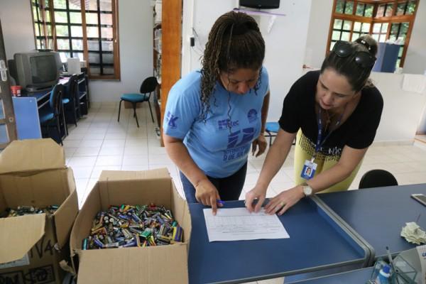 Na imagem duas mulheres separam pilhas e baterias para descarte correto