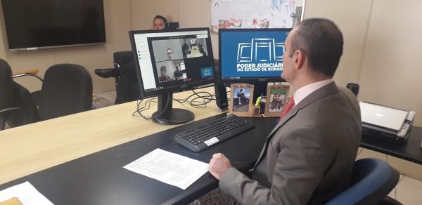 Juiz Air Marin no gabinete iniciando a videoconferência com auxílio de um computador, internet e uma câmera